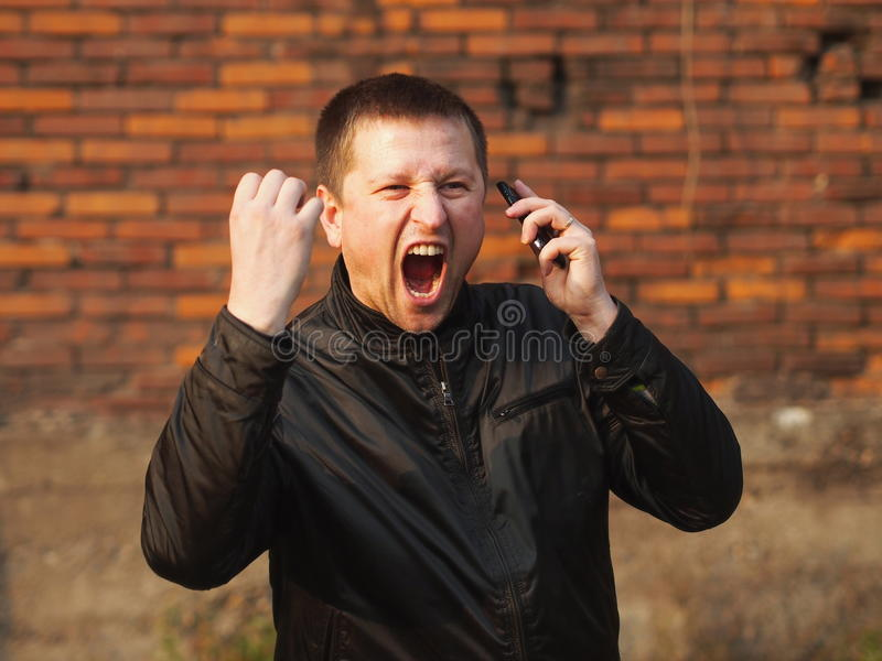 Anger. Man with a cell phone yelling stock image