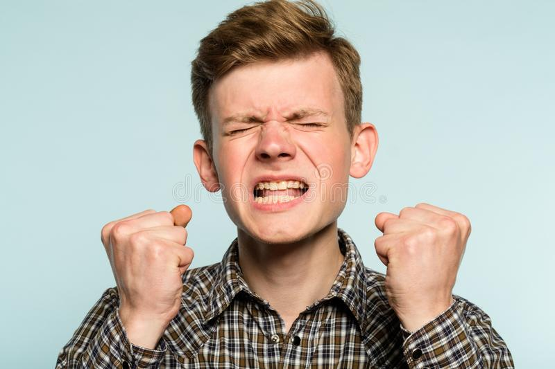 Anger rage hatred infuriated man baring teeth. Anger rage and hatred. enraged infuriated man baring his teeth. portrait of a young guy on light background royalty free stock image