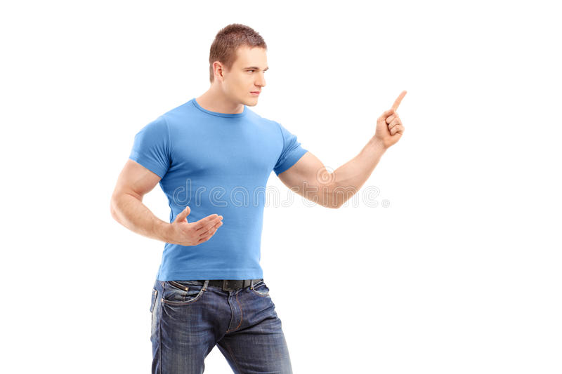 An angry young man pointing with finger and threatening stock photo