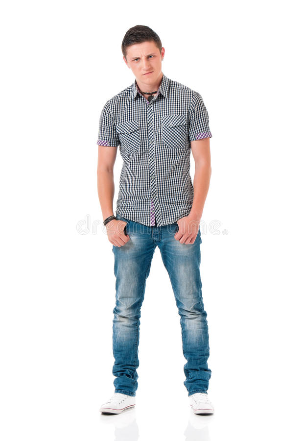 Anger young man. Serious suspicious young man standing with hands in pockets, isolated white background. Full length portrait of anger teen boy stock photography