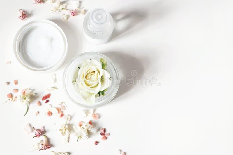 Angeredete Schönheitszusammensetzung Enthäuten Sie Creme, Shampooflasche, trockene Blumen, Rose und Himalajasalz Weißer Tabellenh lizenzfreies stockfoto