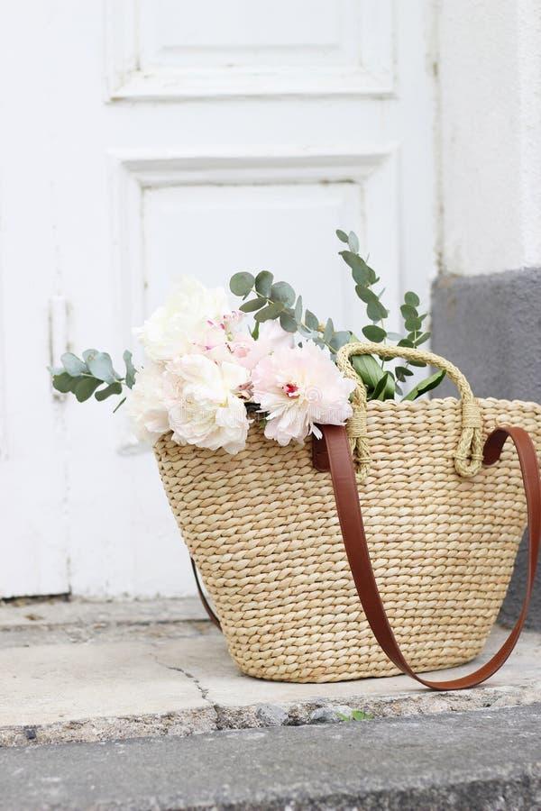 Angeredetes Foto auf Lager Weibliche Hochzeitsstilllebenzusammensetzung mit französischer Korbtasche des Strohs mit rosa Pfingstr lizenzfreie stockbilder