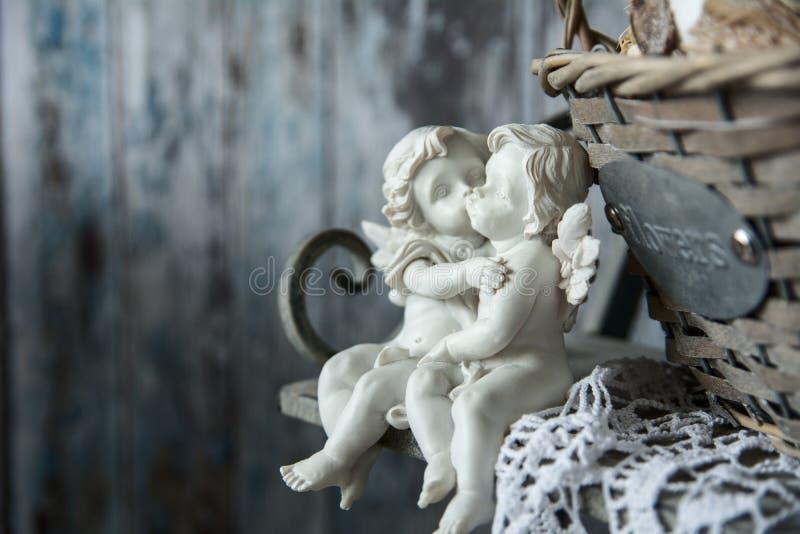 Anges d 39 amour de figurines se reposant sur un banc photo stock image du sensation embrassez - Faire l amour sur un banc ...