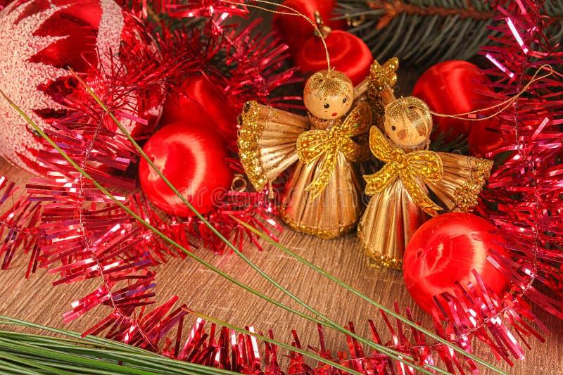 Anges d'or avec la boule rouge avec la branche conifére sur le backgro en bois photographie stock
