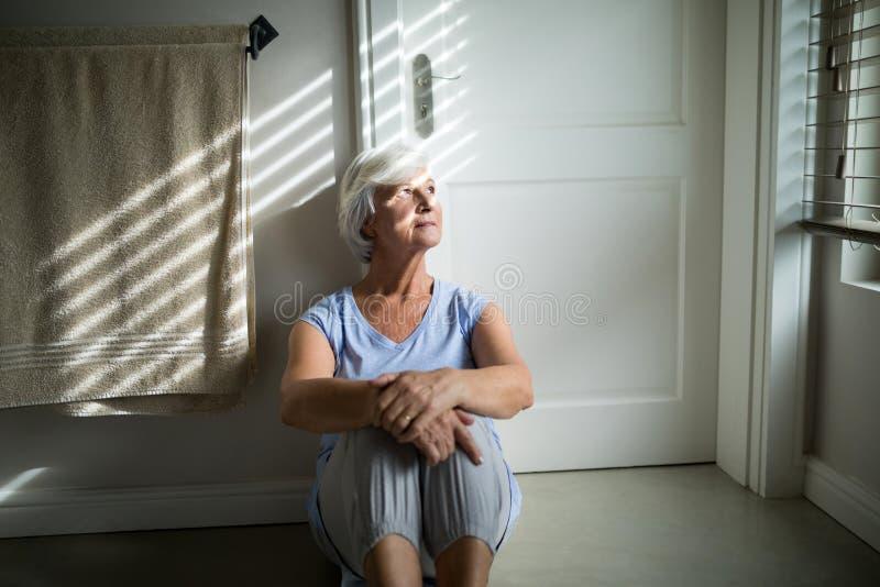 Angespannte ältere Frau, die durch Fenster im Schlafzimmer schaut lizenzfreies stockbild
