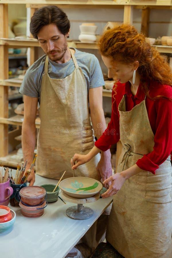 Angesporntes Ingwermädchen in Färbungslehmplatte des roten Hemdes und in hinzufügen Muster stockbild