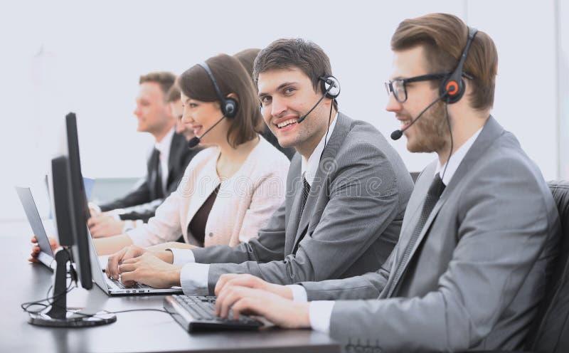 Angestelltcall-center mit Kopfhörer am Arbeitsplatz lizenzfreie stockfotos