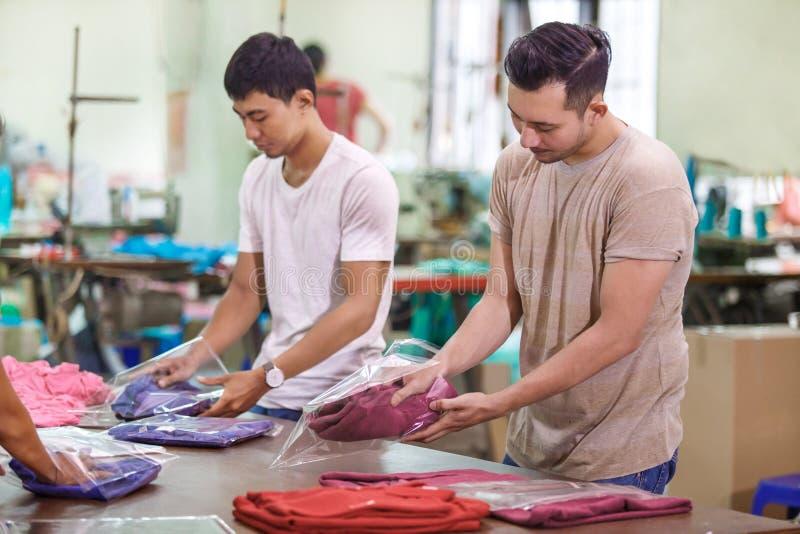 Angestellte in der Textilfabrik, die ihre Produkte verpackt stockfotos