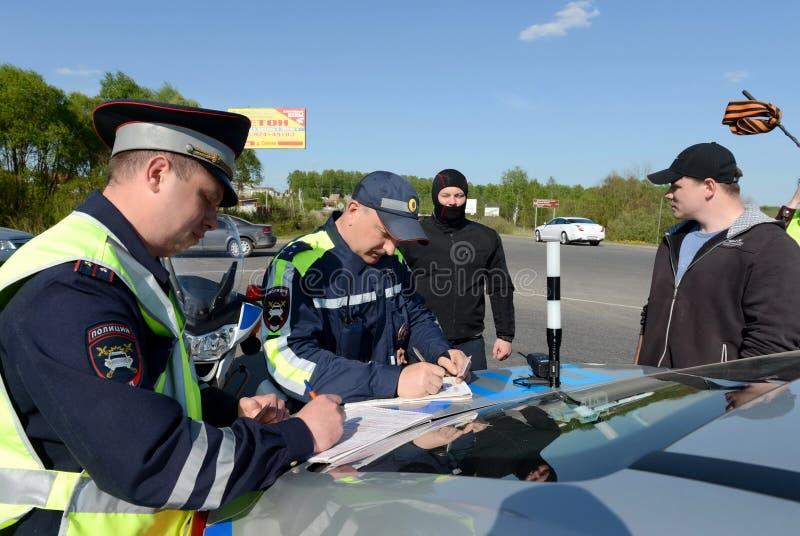 Angestellte des Verkehrspolizeiservices stellt ein Protokoll auf Verletzung von Verkehrsregeln auf lizenzfreies stockfoto