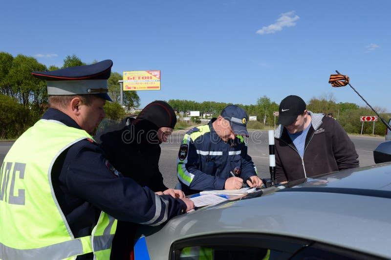 Angestellte des Verkehrspolizeiservices stellt ein Protokoll auf Verletzung von Verkehrsregeln auf lizenzfreie stockfotos