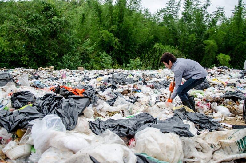 Angestellte und Reiniger sind Verarbeitungsabfall im Dumpstandort am Ra lizenzfreies stockbild
