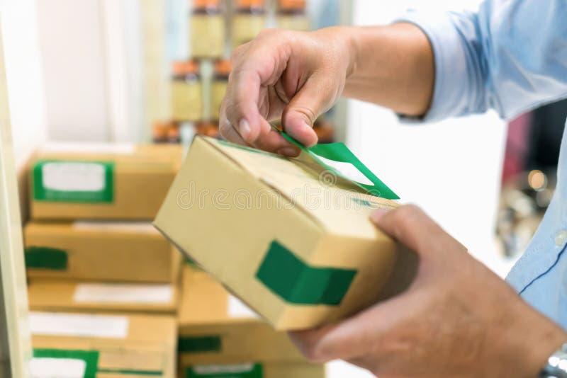 Angestellte verpacken ein Paket im Sendung dem Kunden On-line-Einrichtung zum Vorteil der Kunden stockfotos