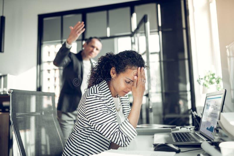 Angestellter, der die Kopfschmerzen h?ren auf ver?rgerten Chef hat stockfotografie
