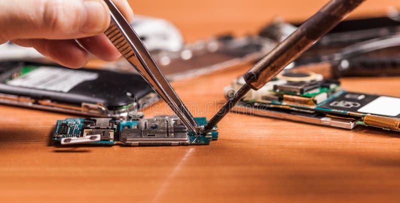 Angestellter, der zerbrochenes Telefon repariert lizenzfreies stockfoto