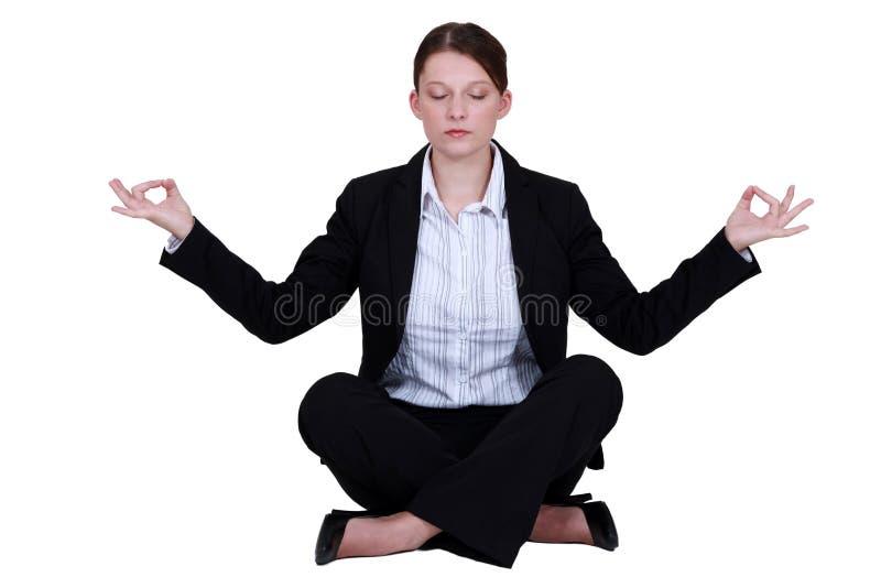 Angestellter in einer Yogaposition stockbild