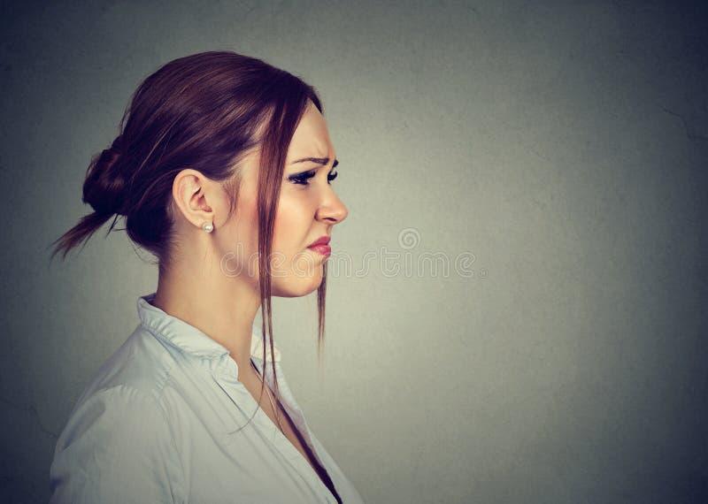 Angewiderte gestörte junge Frau des Seitenprofils stockfoto