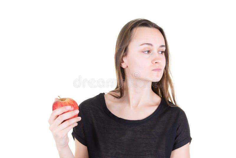 Angewiderte junge Frau, die roten Apfel hält und beiseite in der Anfangsvegetarischen gesunden Diät schaut lizenzfreie stockfotos
