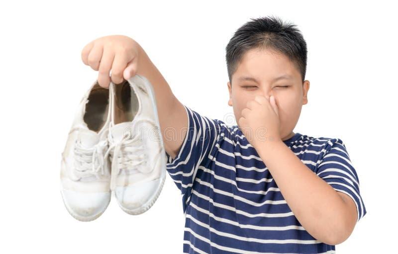 Angewiderter fetter Junge, der ein Paar stinkende Schuhe h?lt stockbilder