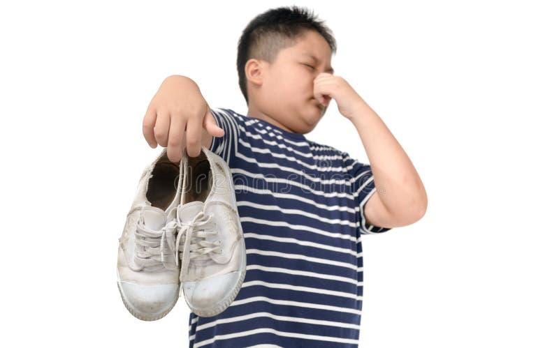 Angewiderter fetter Junge, der ein Paar stinkende Schuhe h?lt lizenzfreie stockbilder
