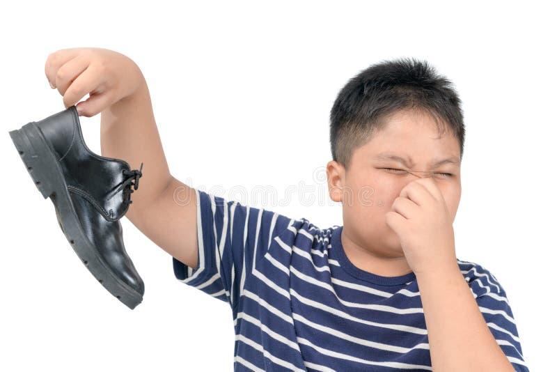Angewiderter Junge, der ein Paar stinkende Lederschuhe h?lt stockfotografie