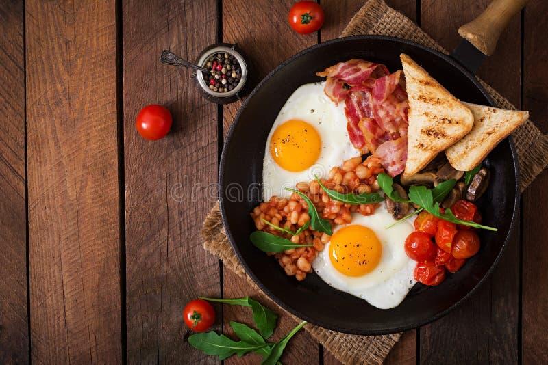 Angielski śniadanie jajko, fasole, pomidory, pieczarki, bekon i grzanka - smażący, zdjęcie royalty free