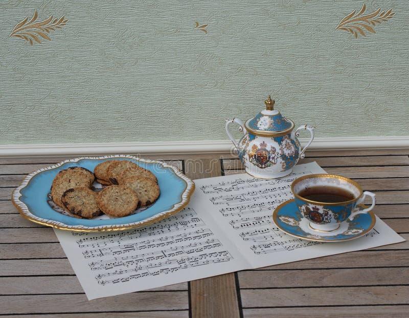 Angielski teacup z spodeczkiem, cukierniczką i tortowym talerzem z ciastkami, świetna kości porcelany porcelana na prześcieradle  obrazy stock