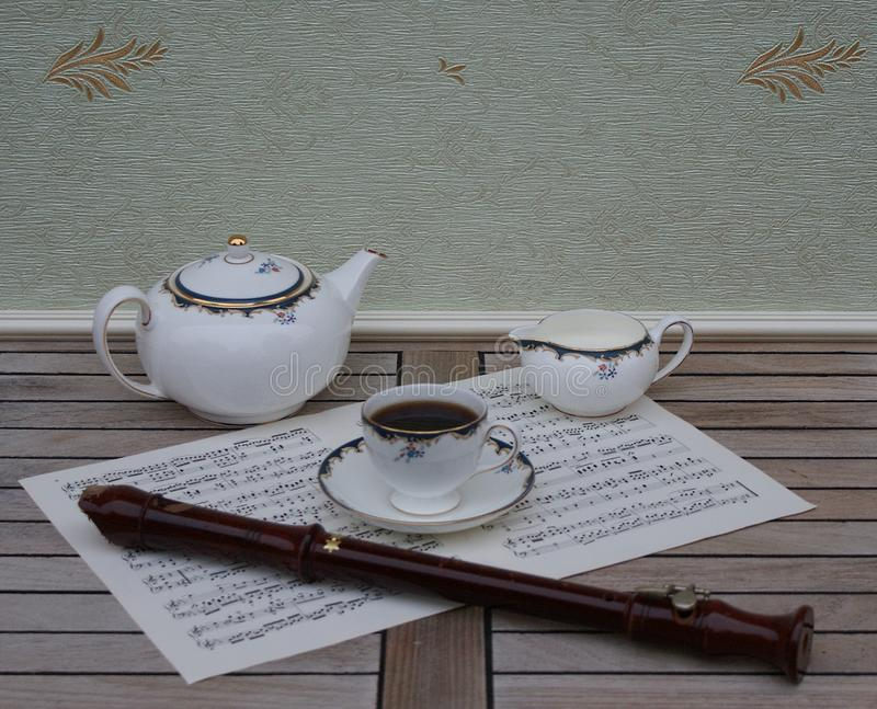 Angielski teacup z spodeczkiem, dzbanek, świetna kości porcelany porcelana i blokowy flet na prześcieradle muzyka, teapot i śmiet obraz stock