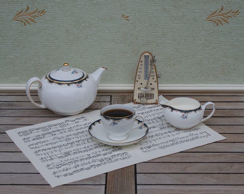Angielski teacup z spodeczkiem, dzbanek, kości porcelany porcelana i metronom dla muzyki na prześcieradle muzyka, teapot i śmieta zdjęcie royalty free