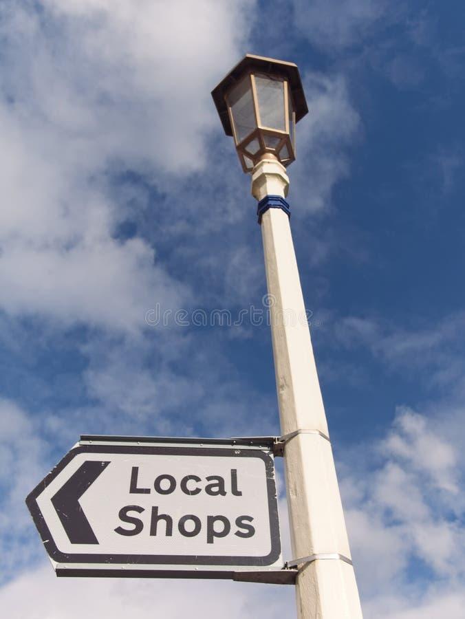 Angielski znak uliczny dla miejscowego Robi zakupy przeciw niebieskiemu niebu z chmury tłem zdjęcie royalty free