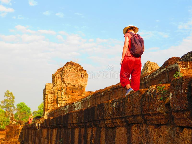 Woman walking on the edge of a wall in Angkor, Cambodia royalty free stock image