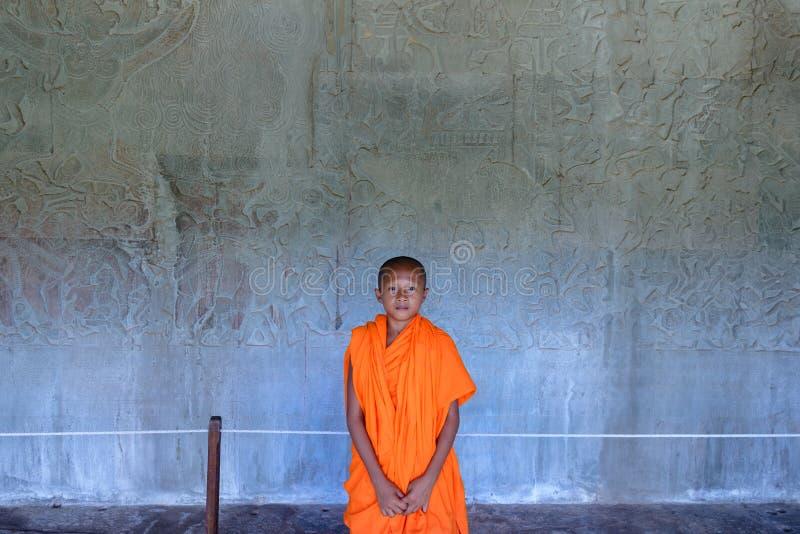 Angkor Cambodja - december 10, 2018: ung stående för buddistisk munk i Angkor Wat, majestätiska tempelbasreliefs i bakgrunden royaltyfri foto