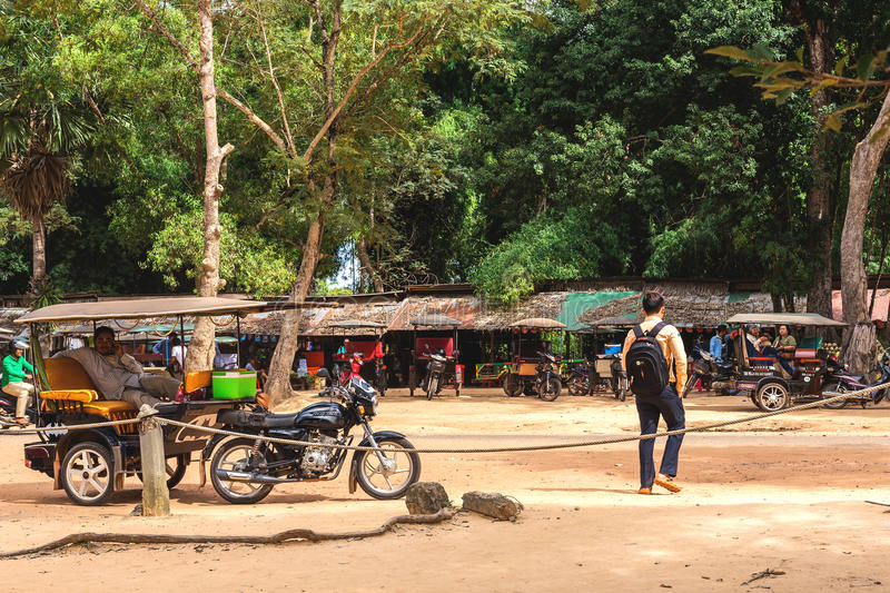 Angkor Wat, Cambodia - December 5, 2016: dealers and tourists. Angkor Wat, Siem Reap, Cambodia - December 5, 2016: dealers and walking tourists at sunny morning stock image