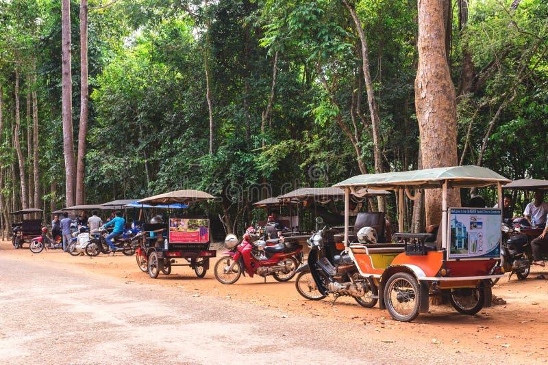 Angkor Wat, Cambodia - December 5, 2016: dealers and tourists. Angkor Wat, Siem Reap, Cambodia - December 5, 2016: dealers and walking tourists at sunny morning stock photos
