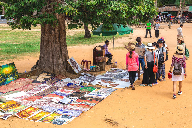 Angkor Wat, Cambodia - December 5, 2016: dealers and tourists. Angkor Wat, Siem Reap, Cambodia - December 5, 2016: dealers and walking tourists at sunny morning stock images