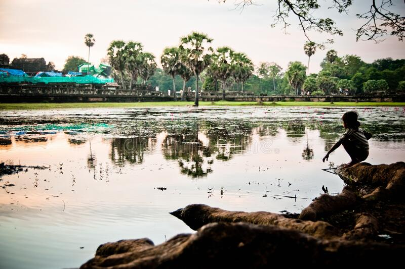 Angkor Wat, Cambodia - 29 October 2011: Cambodian girl looking in loneliness Angkor Wat at sunrise.  stock images
