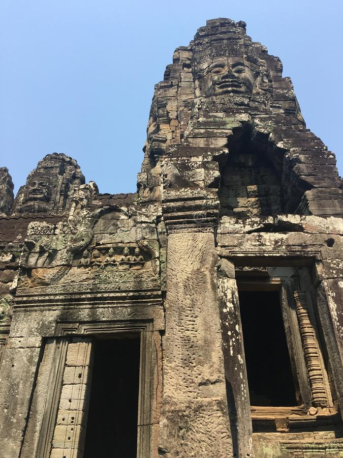 Angkor Wat i Siem Reap, Cambodia Stenframsidor som snidas i det forntida, fördärvar av den Bayon en khmertemplet arkivbild