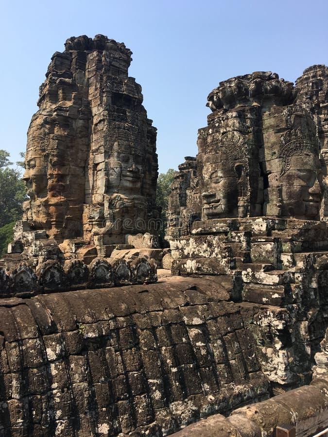 Angkor Wat i Siem Reap, Cambodia Stenframsidor som snidas i det forntida, fördärvar av den Bayon en khmertemplet arkivfoto
