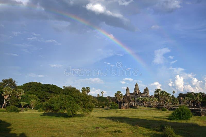Angkor Wat op blauwe hemelachtergrond met mooie regenboog en bos in voorgrond stock fotografie