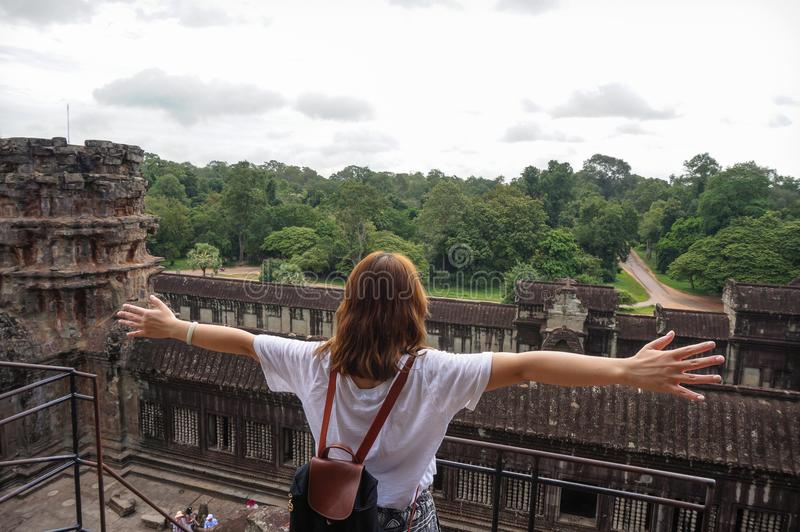 Angkor Wat is an UNESCO World Herutage site since 1992.An Asian woman opens her hands to embrace this beautiful landscape. royalty free stock images