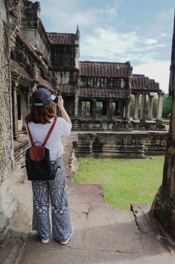 Angkor Wat is an UNESCO World Herutage site since 1992.An Asian woman opens her hands to embrace this beautiful landscape. stock images