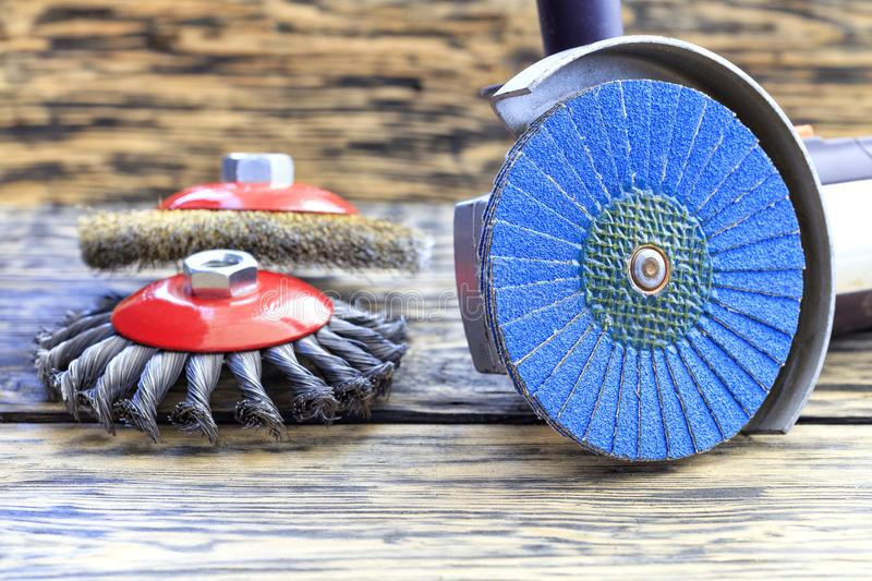 Angle grinder with grinding disc brushes lies on the background of a wooden table stock photo
