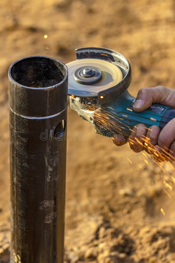 Angle grinder, pipe end. Foundation works. Locksmith royalty free stock image