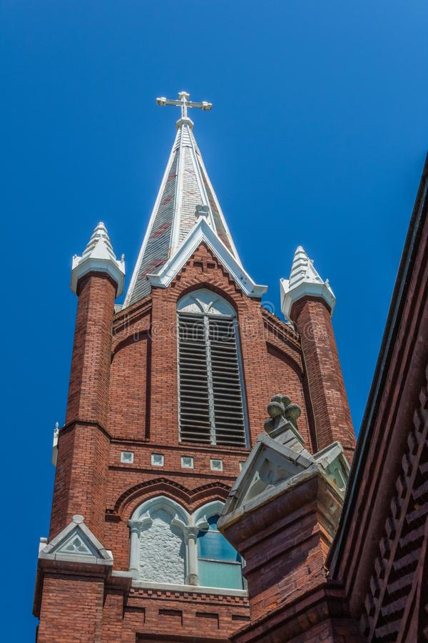 Angle looking up at a steeple with cross against a blue sky, Gothic Revival stock image