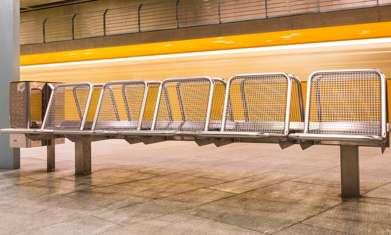 Yellow Train speeding behind metal Seats. Angle perspective of a yellow train speeding behind metal seats in a german subway station royalty free stock photos