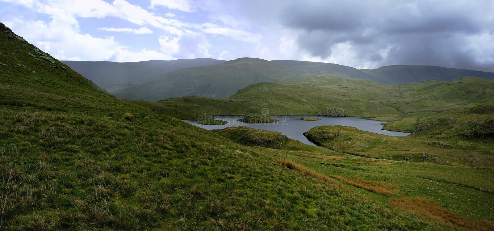 Angle Tarn and the fells. Storm approaching Angle Tarn and the Pikes stock photography