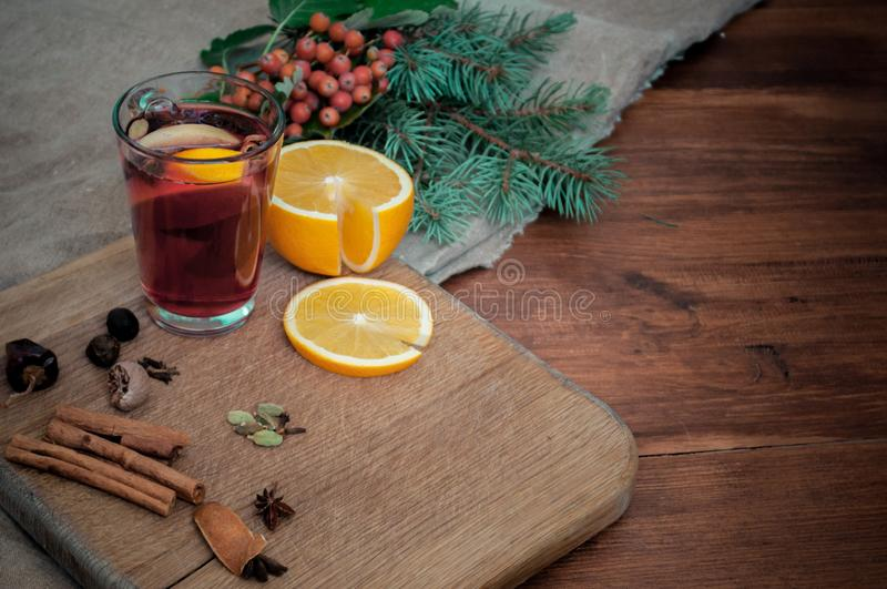 Angle view mulled wine with citrus, cinnamon, cardamon and anise spices and fir. Christmas cozy still life on wooden stock images