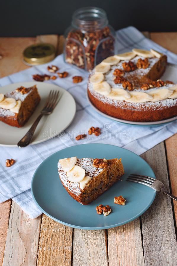 Angle view of sliced banana cake with powdered sugar and walnut on plate with fork. Cozy still life in light tones on wooden backg. Round with checked kitchen royalty free stock photos