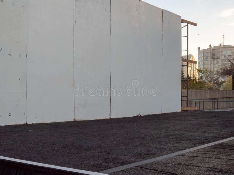 Angled взгляд второпях построенного внешнего этапа с белой стеной стоковое изображение rf