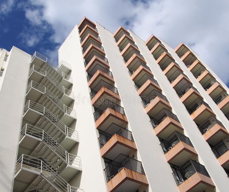 Angled detail view of an old 1960s white concrete apartment building with steps and balconies against blue sky and clouds royalty free stock image