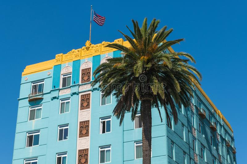 Angled front and side view of a blue art deco style building with yellow trim with an American flag on the rooftop and a palm tree stock photo